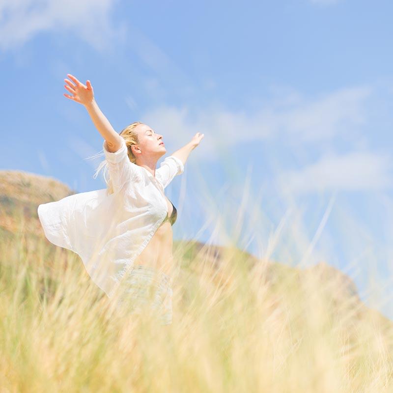 junge frau auf einem berg hebt geniessend die arme zum himmel